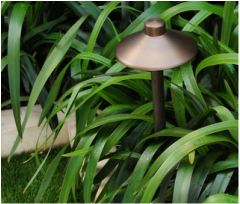 Solid brass LED path light set in grass.