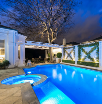 Pool and landscape illuminated with low-voltage LEDs at night.