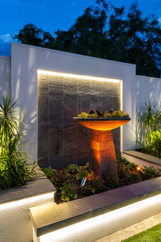This outdoor wall art structure makes use of indirect LED lighting beneath wall rim, as well as set in landscaping.