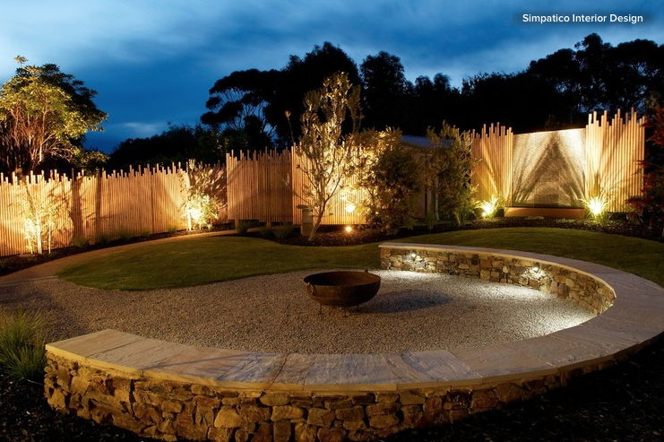 Outdoor lighting led lights illuminate backyard fence and trees while subtle downlights illuminate a