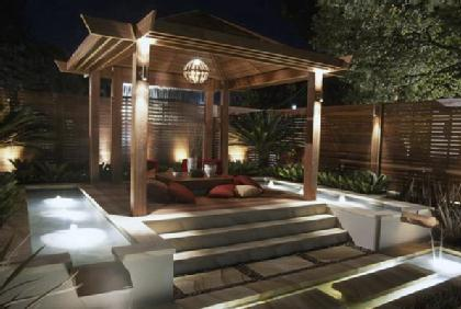Gazebo area outside home with an array of outdoor lighting features.