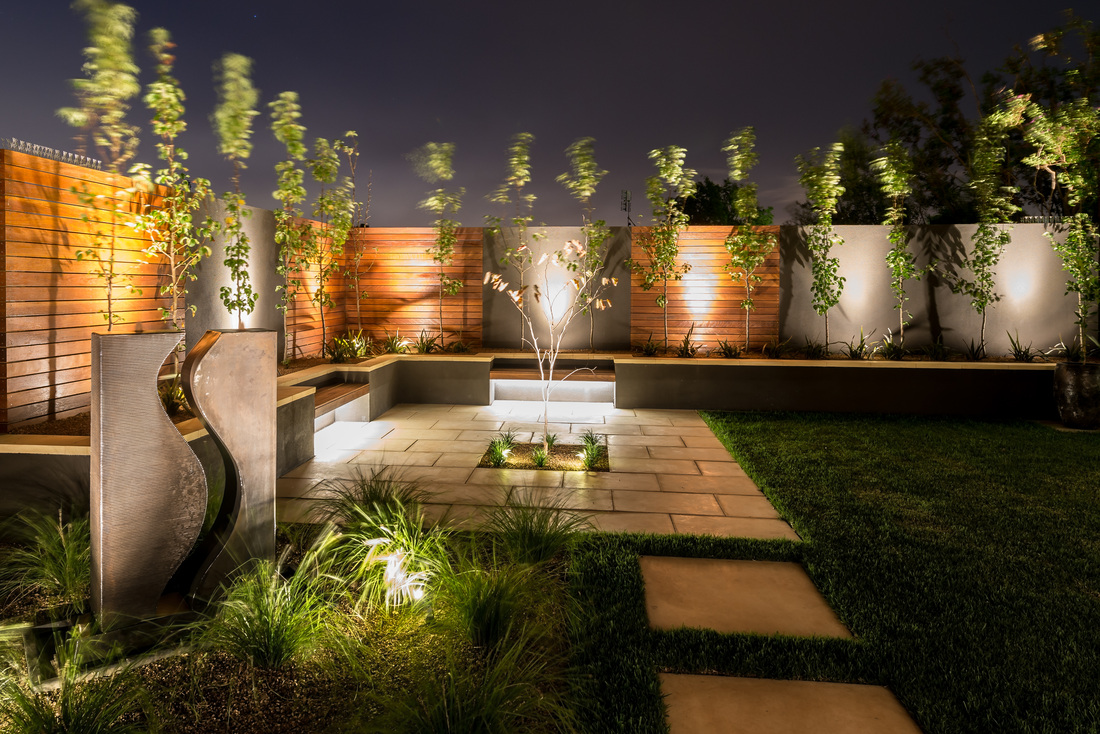 Stylish outdoor living area making creative use of low-voltage LED lighting set in plants, along walls and beneath trees.