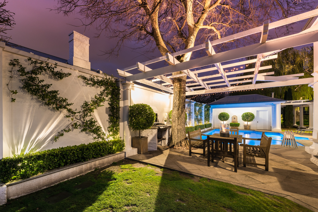 Finished outdoor living area on home featuring pool, patio, arbor, wall planters and indirect and direct LED lighting for nighttime.